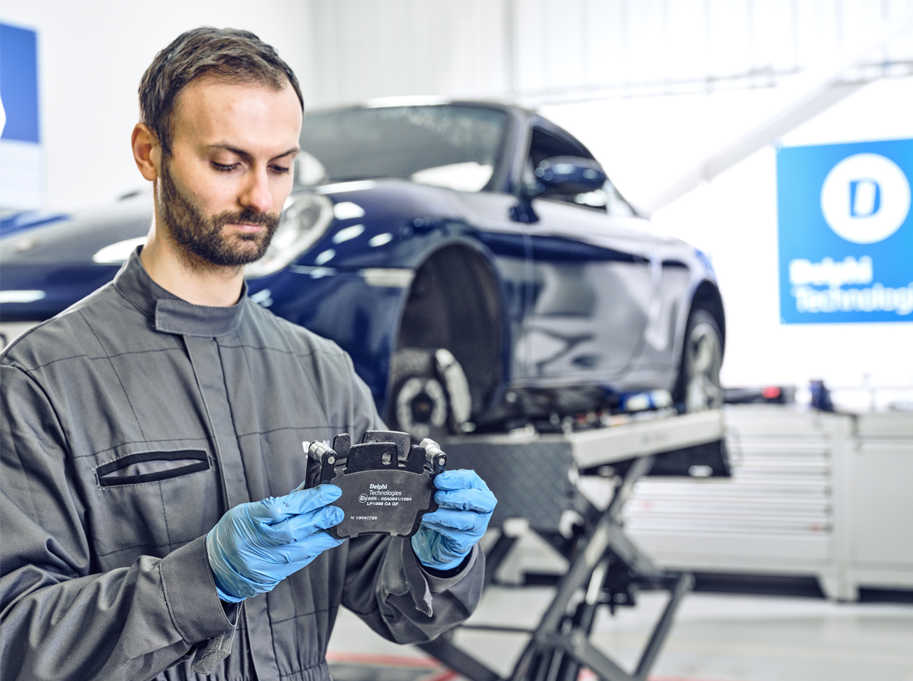 Man in garage holding Delphi Technologies brake pad with a Porsche on a lift behind him