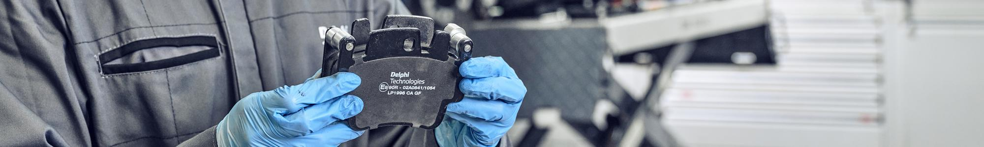 A man with gloves holding a Delphi Technologies brake pad in a workshop.