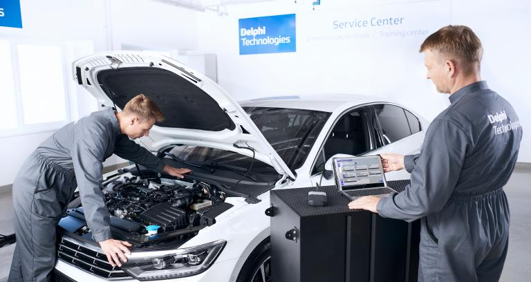 Two Delphi Technologies technicians working on a car in a garage with a DS-nano scan tool