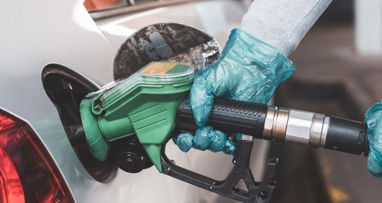 Hands with PPE gloves filling up car fuel tank at a gas station