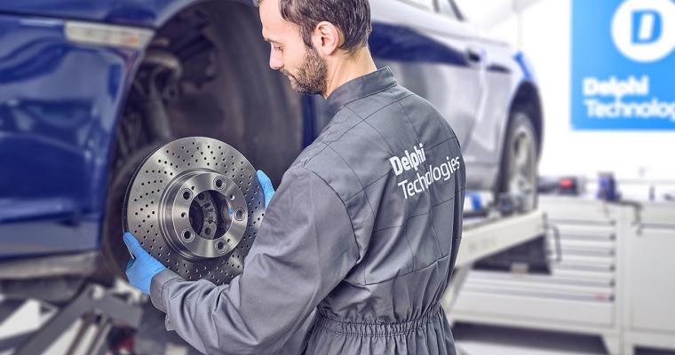 Technician with Delphi Technologies logo on back holds brake disc in front of a blue vehicle