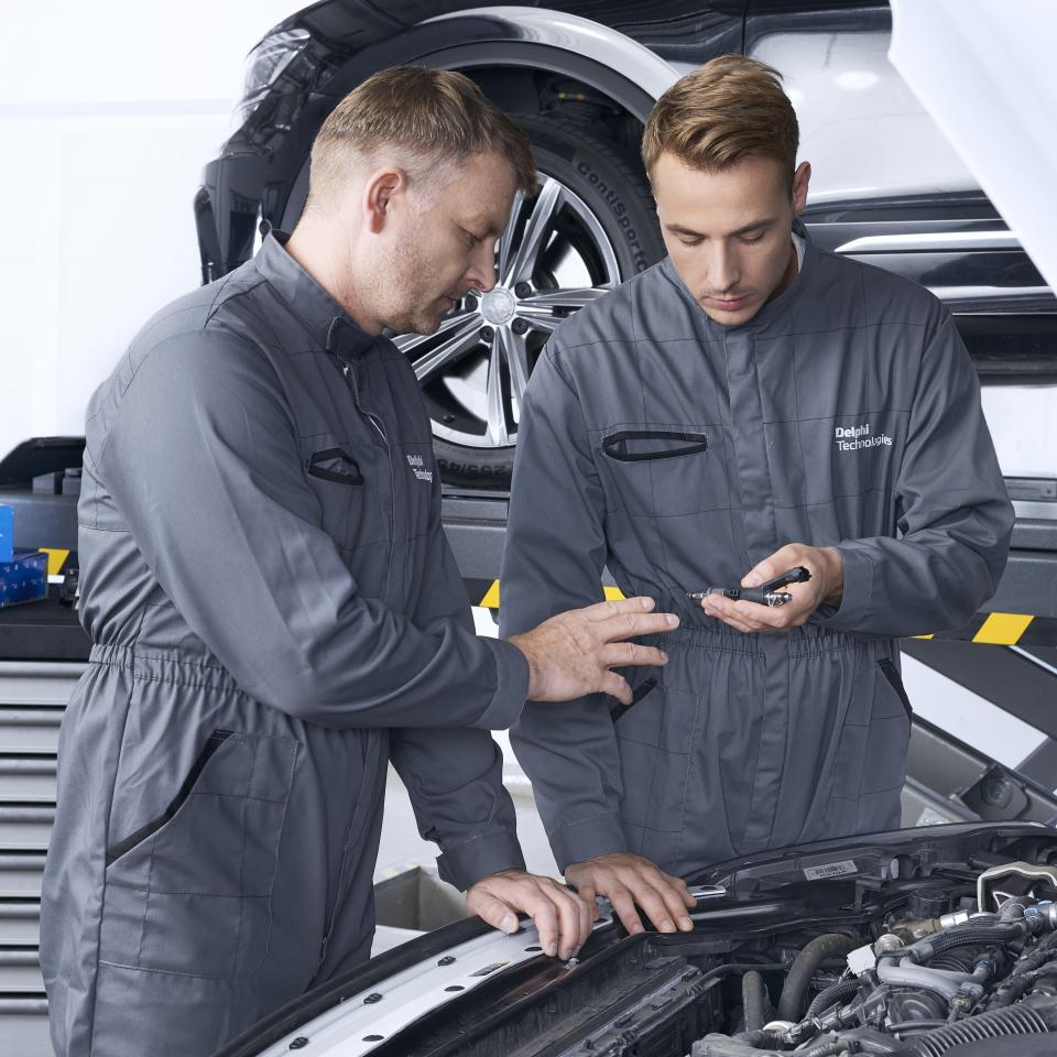 Two technicians looking auto parts under a car hood