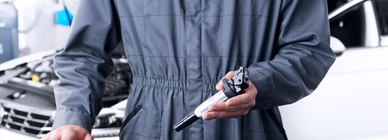 A man holding an ignition coil wearing a Delphi Technologies uniform